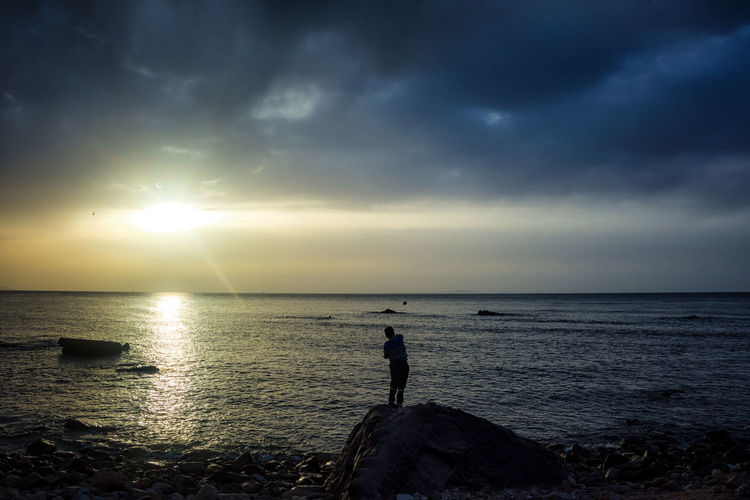 Adult Adults Only Beach Beauty In Nature Day Horizon Over Water Nature One Person One Woman Only Only Women Outdoors People Real People Rock - Object Scenics Sea Silhouette Sky Sunset Tranquil Scene Tranquility Water