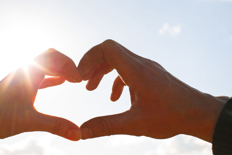 Cropped hands making heart shape against sky