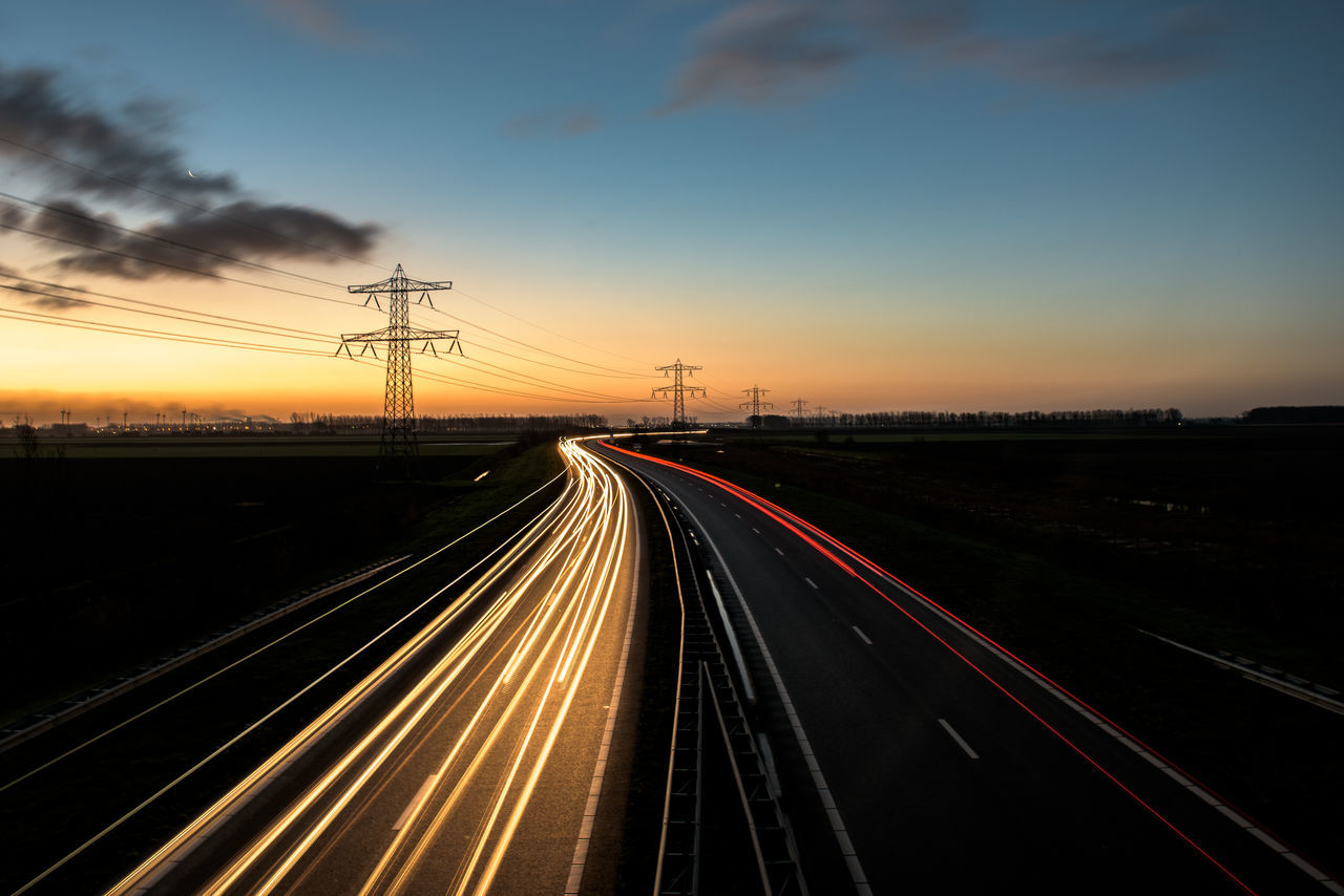 Light trails on road against sky during sunset