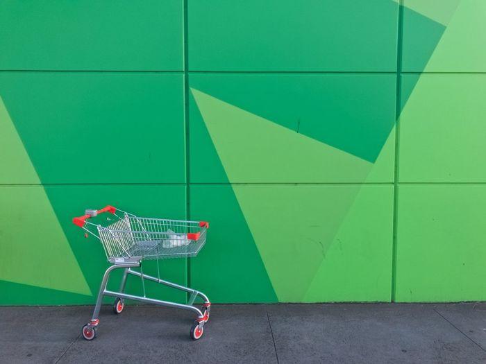 Shopping cart against green wall