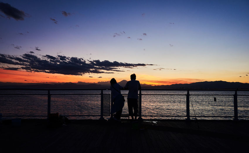 Couple - Relationship Togetherness Beauty In Nature Leisure Activity Lifestyles Looking At View Men Nature Orange Color Outdoors Positive Emotion Real People Rear View Scenics - Nature Sea Silhouette Sky Standing Sunset Togetherness Tranquility Two People Water HUAWEI Photo Award: After Dark Tranquil Scene Scenics Horizon Over Water Observation Point Coast Idyllic #urbanana: The Urban Playground