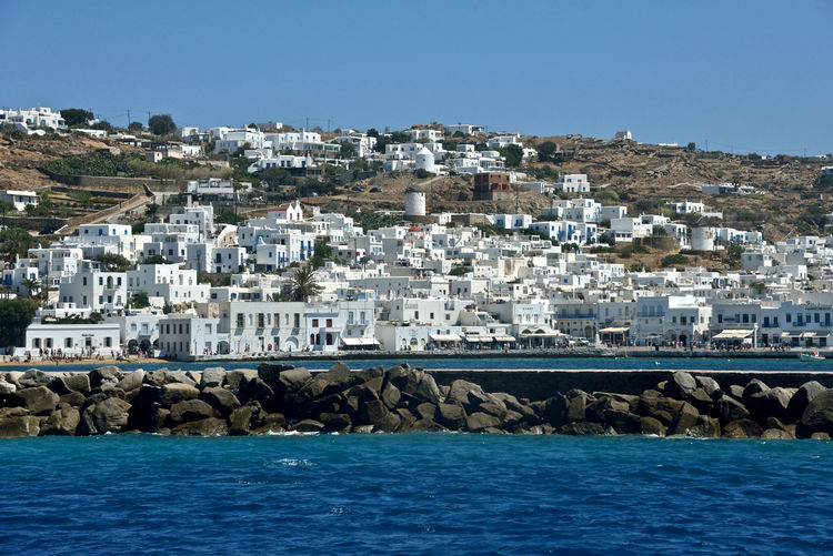 panoramic seaside view of Mykonos with white buildings and pier made of rocks Building Exterior Water Built Structure Sea Building Architecture Residential District Sky City Blue Rock Nature No People Waterfront Day Clear Sky Outdoors Rock - Object TOWNSCAPE Mykonos,Greece Panoramic View Greek Architecture Pier Bay Travel Travel Destinations Panorama Lifestyles Holiday