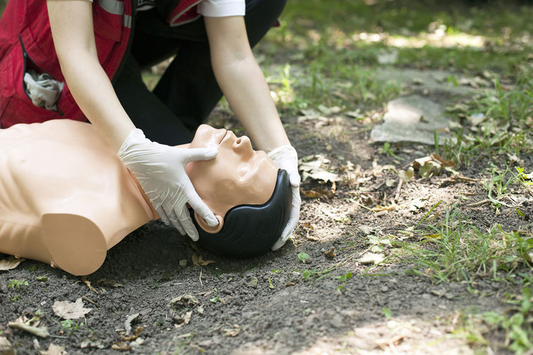 Low section of woman practicing on cpr dummy at field