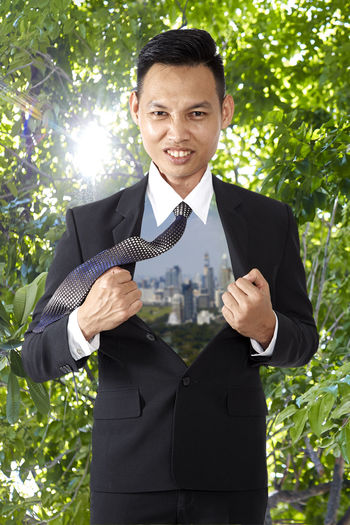 Portrait of smiling businessman standing against trees