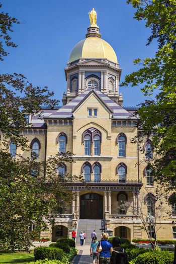 University of Notre Dame USA Color Green Blue Sky Culture Science And Technology Campus Education Famous Green Grass Knowledge Lawn Tree Vertical Composition Christian Golden Tower Building Main Building Notre Dame Outdoor Religion Sculpture Sunny Day University Of Notre Dame USA