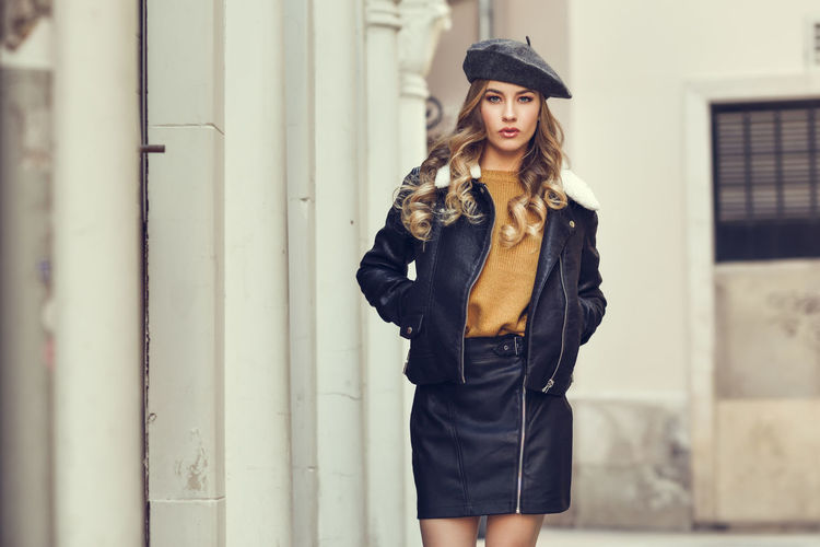 Blonde woman in urban background. Beautiful young girl wearing black leather jacket and mini skirt standing in the street. Pretty russian female with long wavy hair hairstyle and blue eyes. Fashion Architectural Column Beautiful Woman Beauty Black Color Clothing Contemplation Fashion Front View Hair Hairstyle Hat Leather Leisure Activity Looking At Camera One Person Outdoors Portrait Real People Russian Girl Standing Three Quarter Length Women Young Adult Young Women
