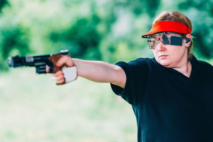 Sport Shooting Training. Woman Shooting Target Shooting Pistol Sport Shooting Gun Target Weapon Practicing Sports Training Training Female Woman Outdoor Barrel Competitive Sport Competition Protective Eyewear Handgun Concentration Technique Aiming Holding Serious Caucasian Ethnicity 30-39 Years Green Color