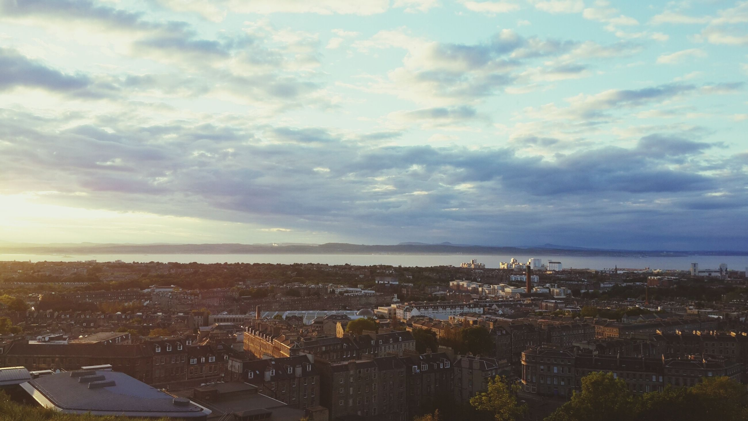 building exterior, architecture, built structure, cityscape, sky, city, cloud - sky, high angle view, crowded, residential district, residential building, sea, residential structure, cloudy, water, cloud, horizon over water, town, aerial view, house