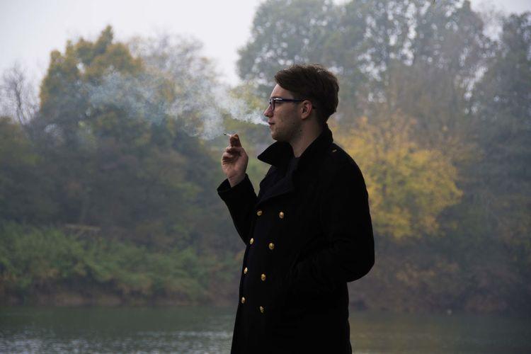Young man smoking by lake
