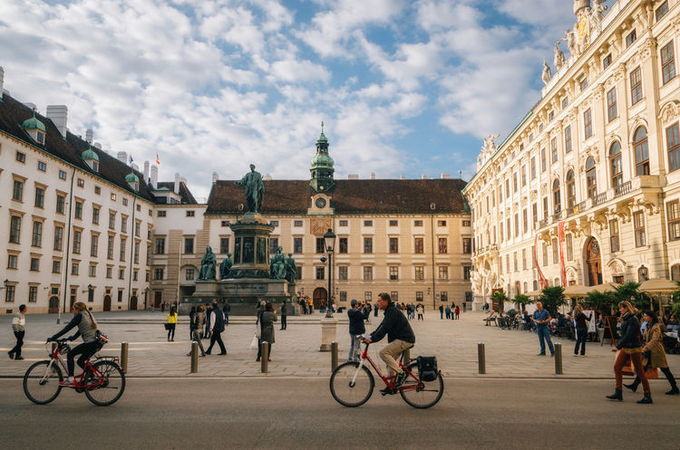 Vienna, Austria. Tourists walk and ride bicycles against monument to Francis II at the In der Burg square of Hofburg palace in evening Austria ❤ Square Vienna Architecture Bicycle Building Exterior Built Structure City Mode Of Transportation Outdoors Real People Sky Street Transportation Travel Destinations