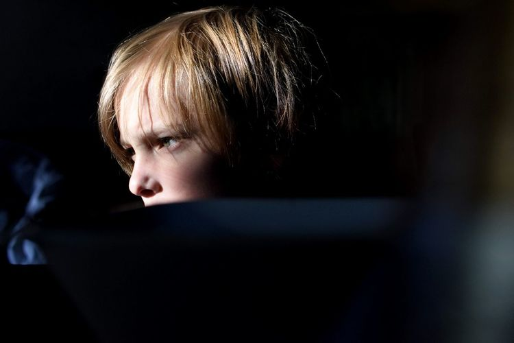 Close-up of thoughtful boy looking away in darkroom
