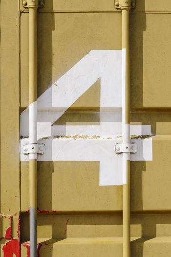 White silk-screen printing of number 4 on a mustard-colored shipping container