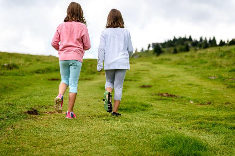 Rear view of women walking on grass
