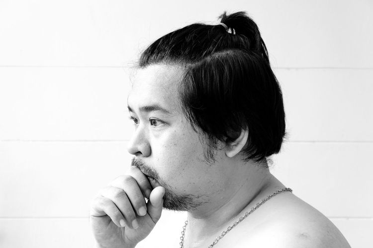 Close-up of sumo standing against wall