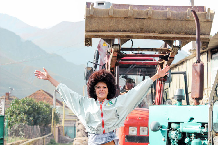 Portrait of happy young woman with arms outstretched standing against bulldozer