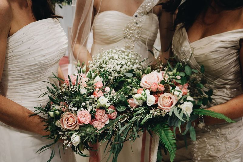 Midsection of bride with bridesmaid holding bouquet while standing in wedding ceremony