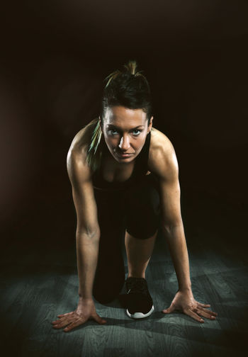 Portrait of beautiful athletic woman posing ready to run over dark background Black Background Brave Entrepreneurship Looking At Camera Ready To Go Slim WILLPOWER Active Lifestyle  Athlete Beautiful Woman Blonde Girl Empowerment  Exercising Fit Fitness Training Healthy Lifestyle Muscular Build One Person Portrait Runner Sport Start Vertical Young Adult Young Women