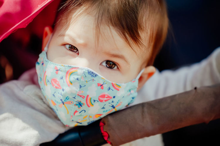 Close-up portrait of cute baby girl wearing mask