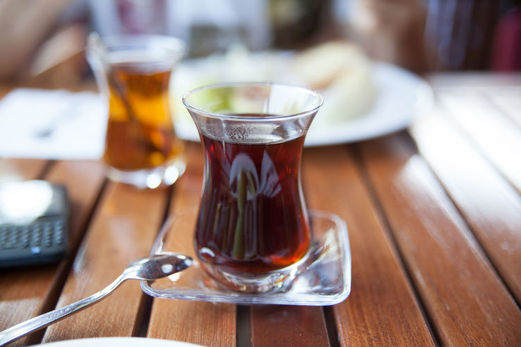 Black tea in glass on wooden table