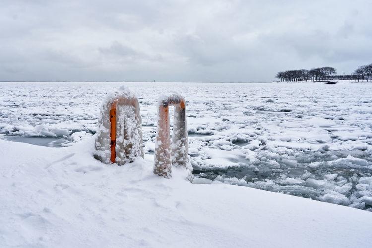 Wooden posts on frozen sea against sky