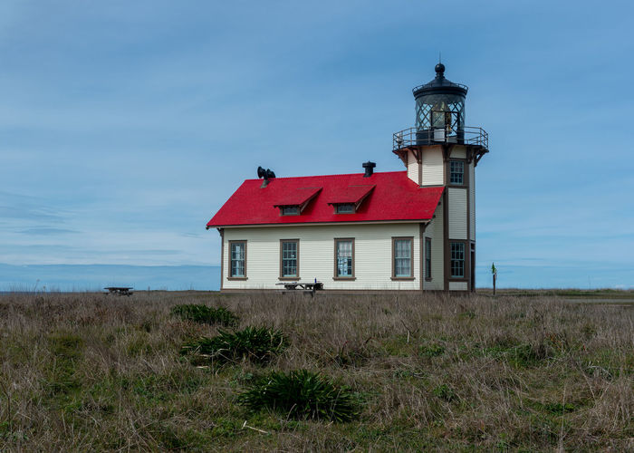 House on field by lighthouse against sky
