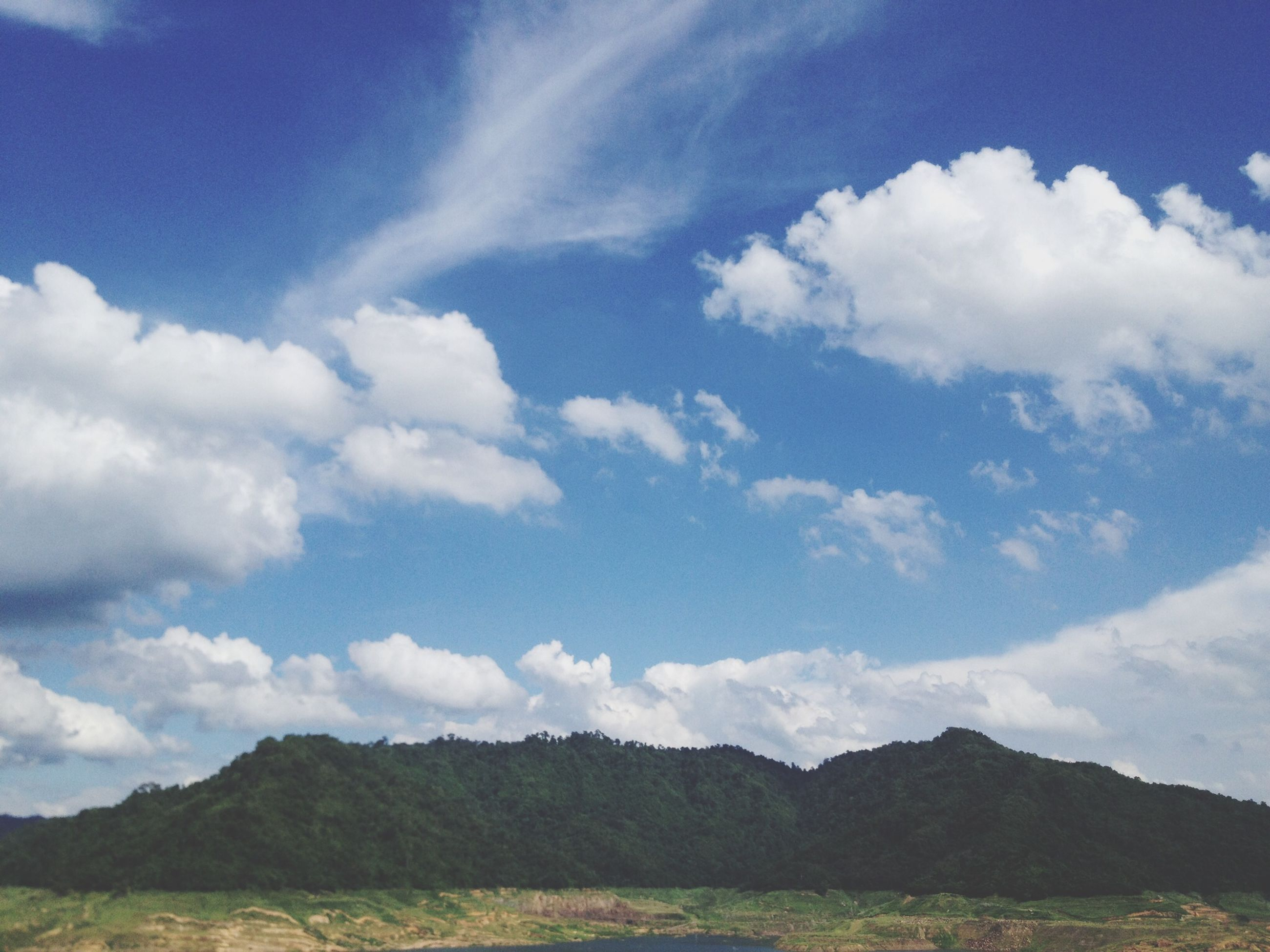 sky, landscape, tranquil scene, tranquility, scenics, mountain, beauty in nature, cloud - sky, nature, cloud, blue, non-urban scene, field, remote, mountain range, grass, idyllic, day, horizon over land, hill