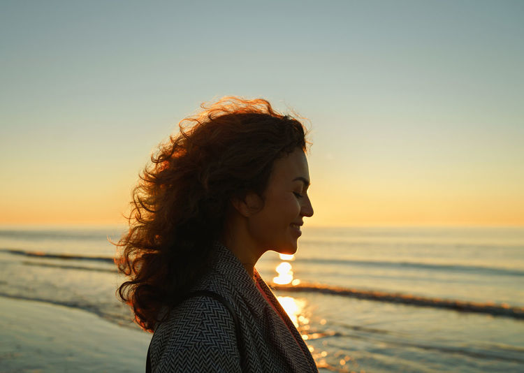 Woman looking at sea shore against sky during sunset