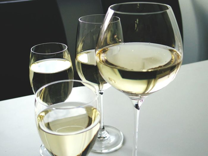 High angle view of white wine in glasses on table