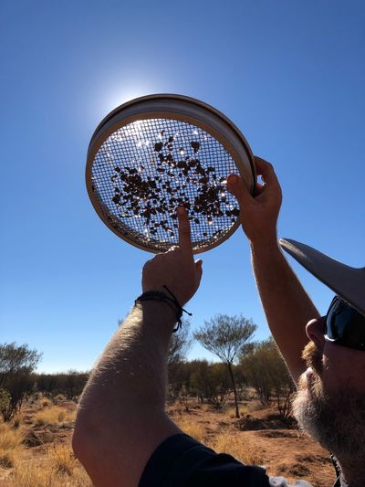 Close-up of man holding strainer on field against clear sky