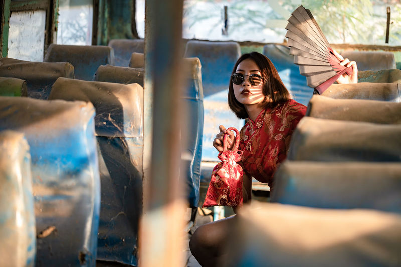 Portrait of smiling young woman sitting in abandoned bus