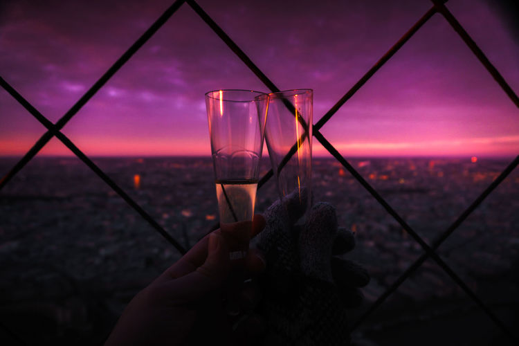Cropped Image Of People Toasting Champagne Flutes Against Sky At Twilight