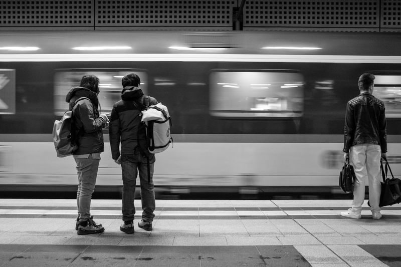 Men Waiting At Railroad Station Platform
