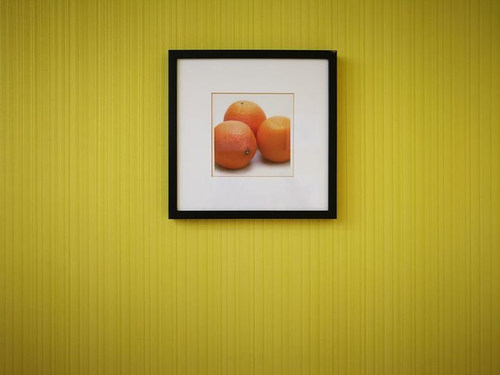 Close-up of fruit on table against orange wall