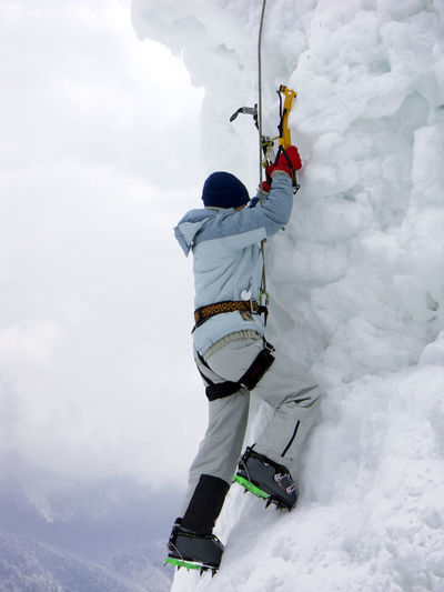 Low angle view of person climbing on snow