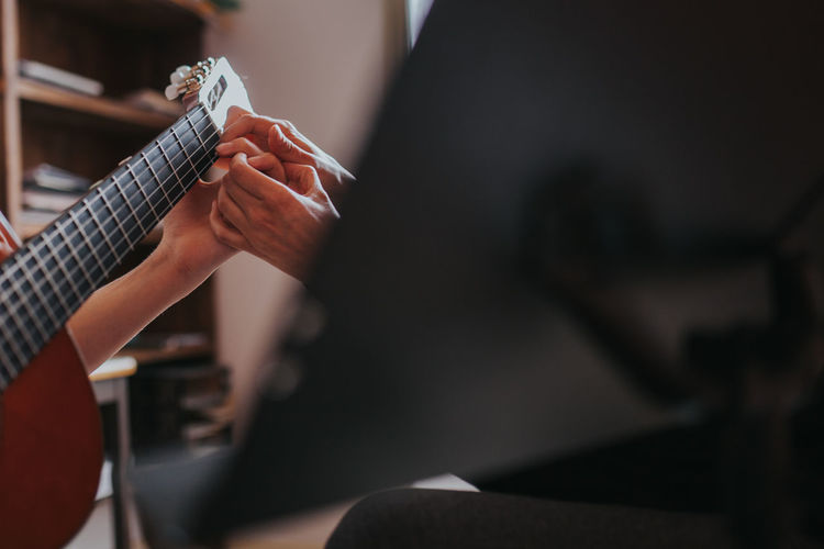 Cropped image of teacher teaching student to play guitar in classroom