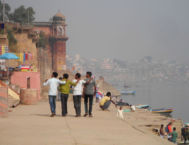 """Varanasi is a city in the Indian state of Uttar Pradesh dating to the 11th century B.C.E. Regarded as the spiritual capital of India, the city draws pilgrims who bathe in the River Ganges' sacred waters and perform funeral rites. Along its winding streets are some 2,000 temples, including Kashi Vishwanath, the """"Golden Temple,"""" dedicated to the Hindu god Shiva. Clear Sky Famous Place Ganges River Group Of People Lifestyles Men Outdoors Place Of Worship Rear View Tourism Travel Destinations Varanasi Varanassi Walking"""