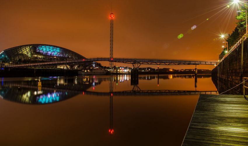 Bridge Over Clyde River By Modern Building Against Sky At Night