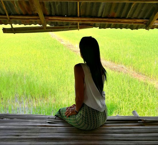 Woman sitting on table against grassy field