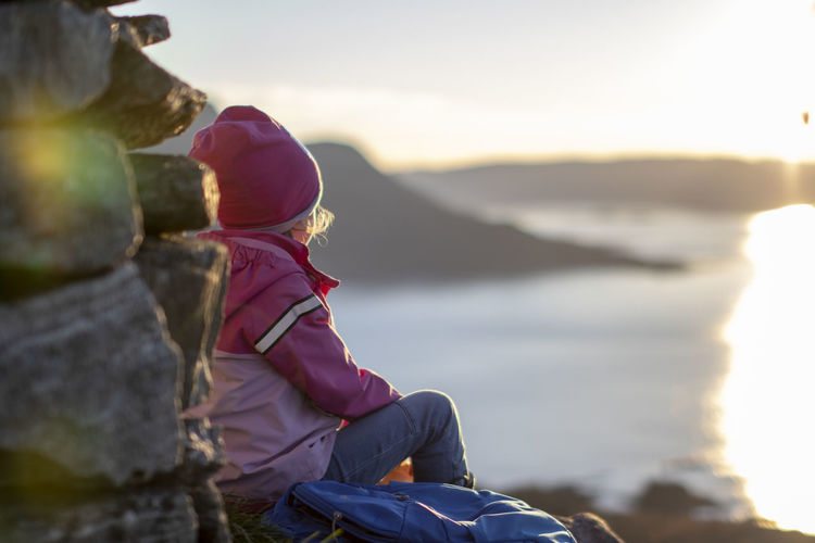 Chlid on the top. One Person Mountain Real People Leisure Activity Nature Sky Sitting Water Solid Lifestyles Rock Rock - Object Casual Clothing Beauty In Nature Women Sunlight Day Childhood Mountain Range Looking At View Outdoors