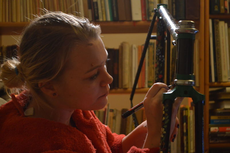 Woman painting bicycle frame against bookshelf