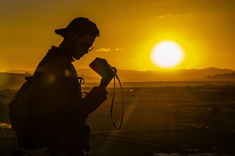 Silhouette man photographing at sunset