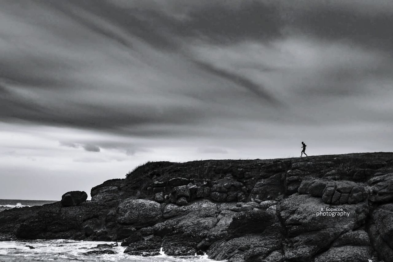rock - object, rock formation, nature, sky, cloud - sky, one person, beauty in nature, scenics, tranquility, full length, outdoors, cliff, landscape, sea, silhouette, day, adventure, standing, real people, one man only, adult, people
