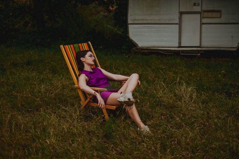 Woman Sitting On Chair Over Field