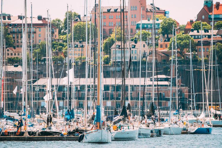 Sailboats moored at harbor in city