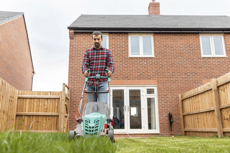 Full length of man standing outside house in yard