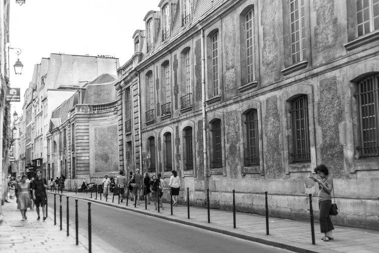 People Walking On Road Along Buildings In City