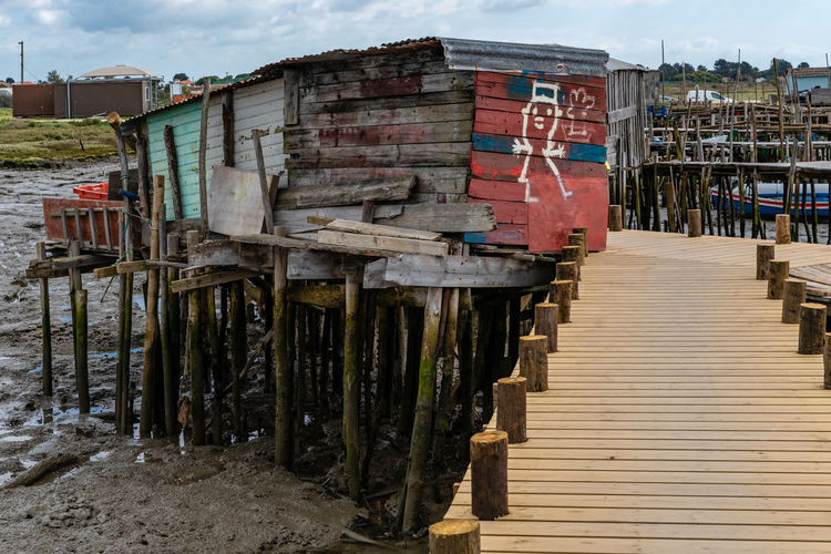 Wooden pier on beach by houses against sky