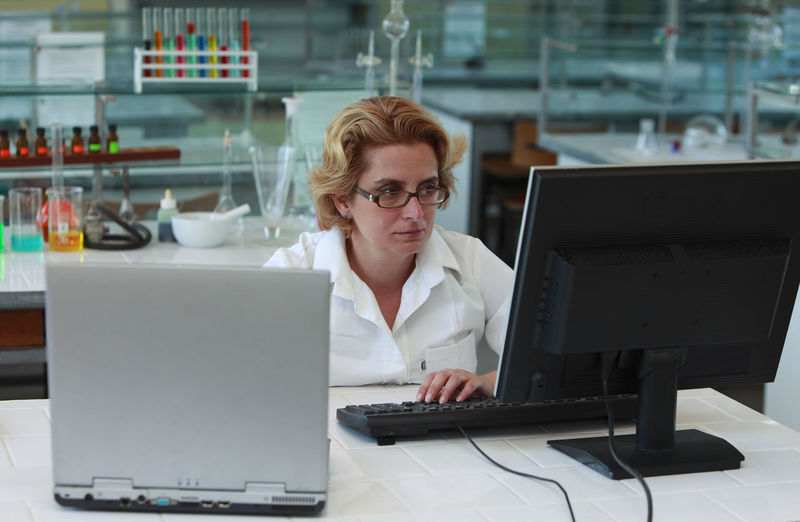 Female researcher working in a lab with computer in front of her. Research Science Scientist Adult Business Computer Concentration Eyeglasses  Female Researcher Front View Indoors  Lab Laboratory Laptop One Person Researcher Researcher Life Table Technology Using Laptop Wireless Technology Working