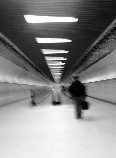 Blurred motion of man walking on illuminated subway station