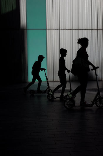 Silhouette of three people on scooters